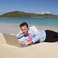 Relaxed businessman relaxing on tropical beach with his feet in the water surfing the internet on a laptop